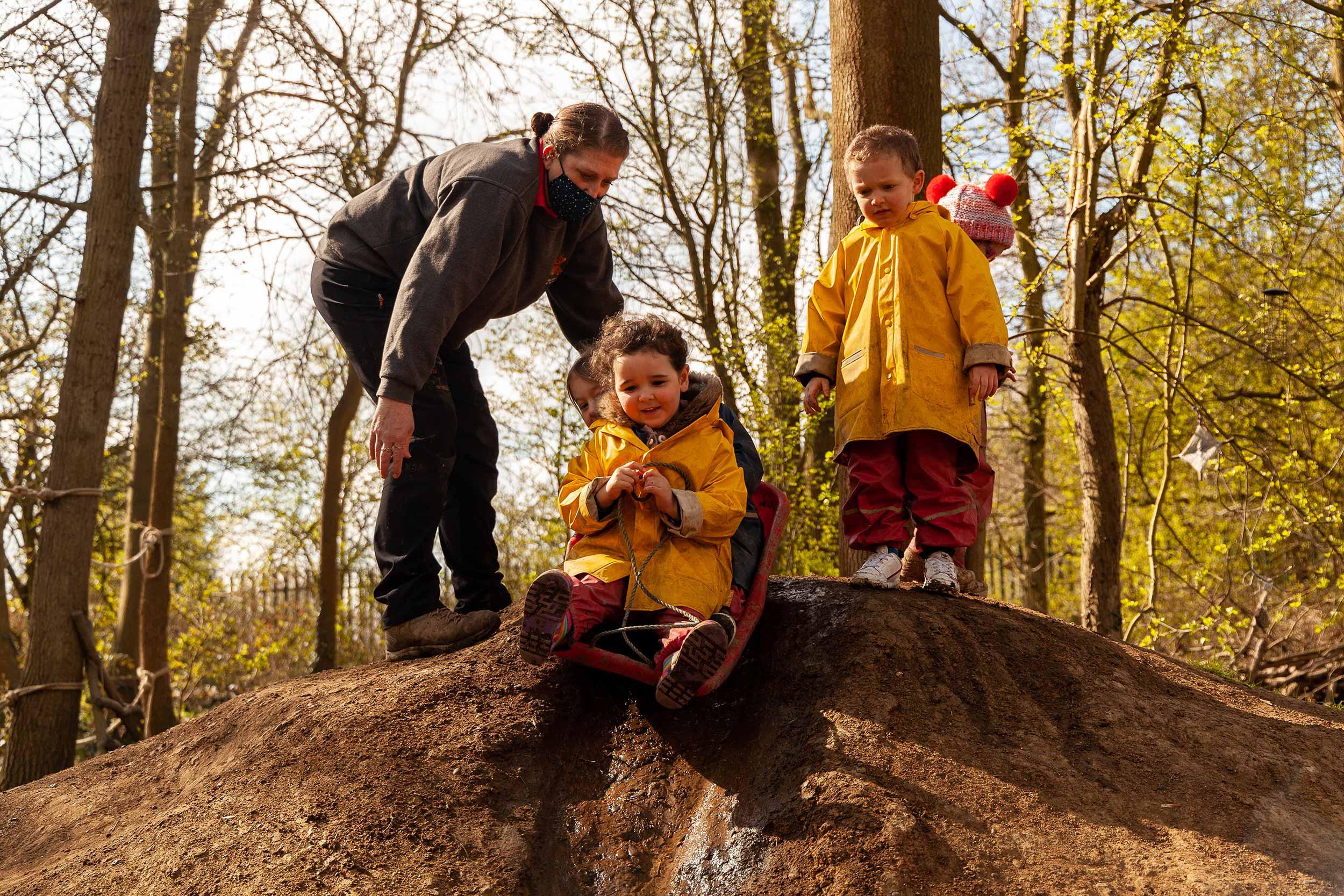 Children sliding down a mud hill