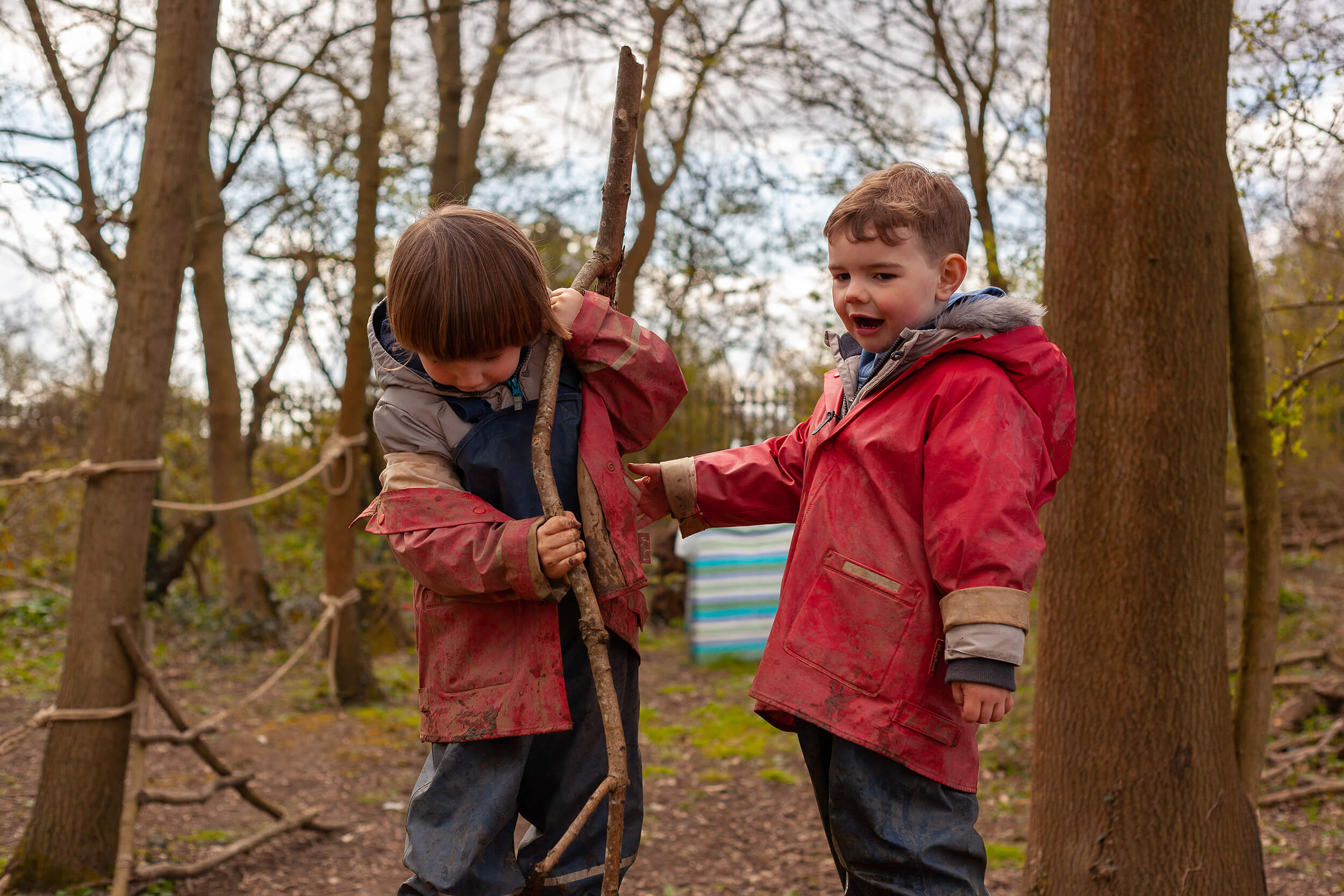 2 boys playing in the woods