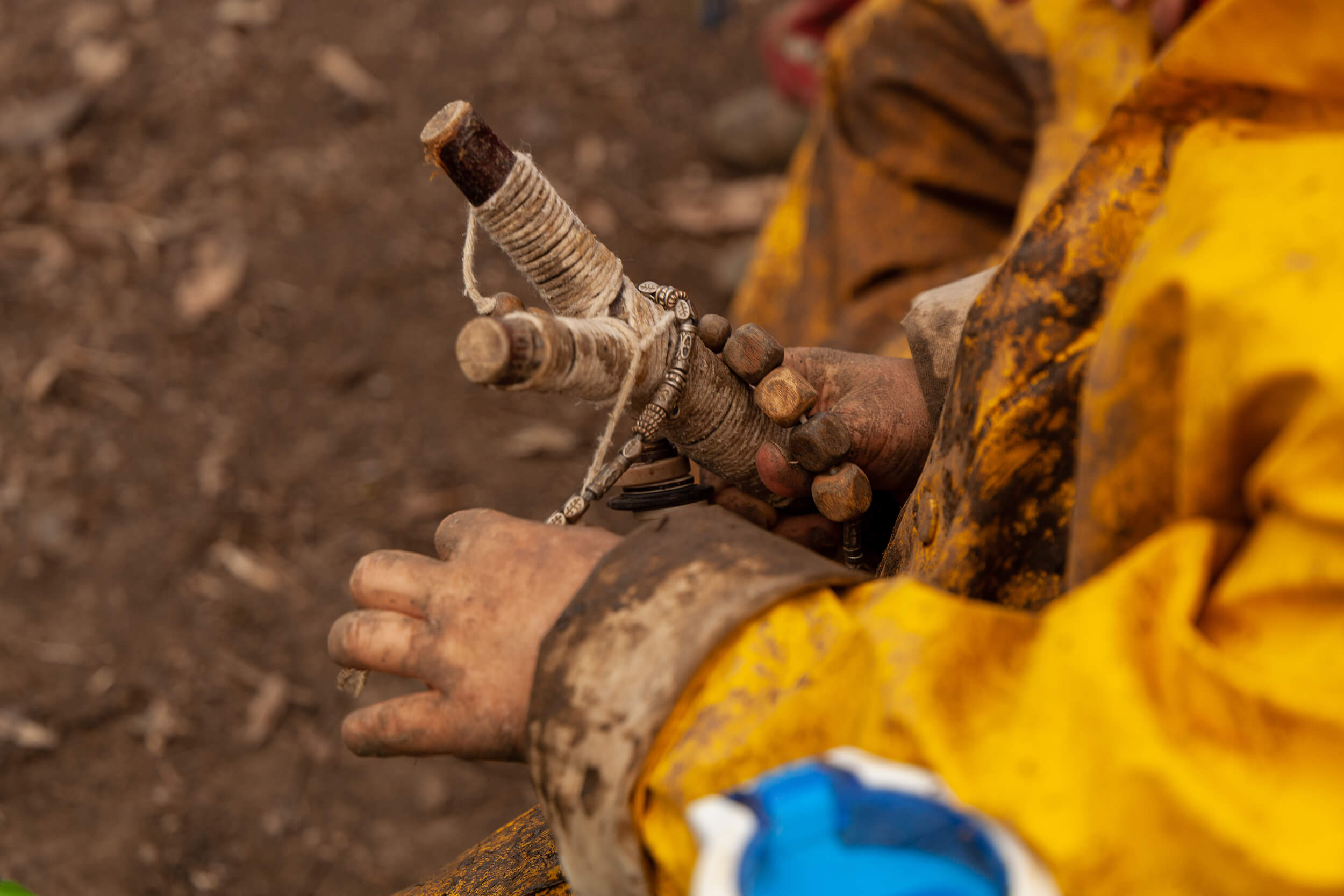 Muddy hands holding a wooden toy