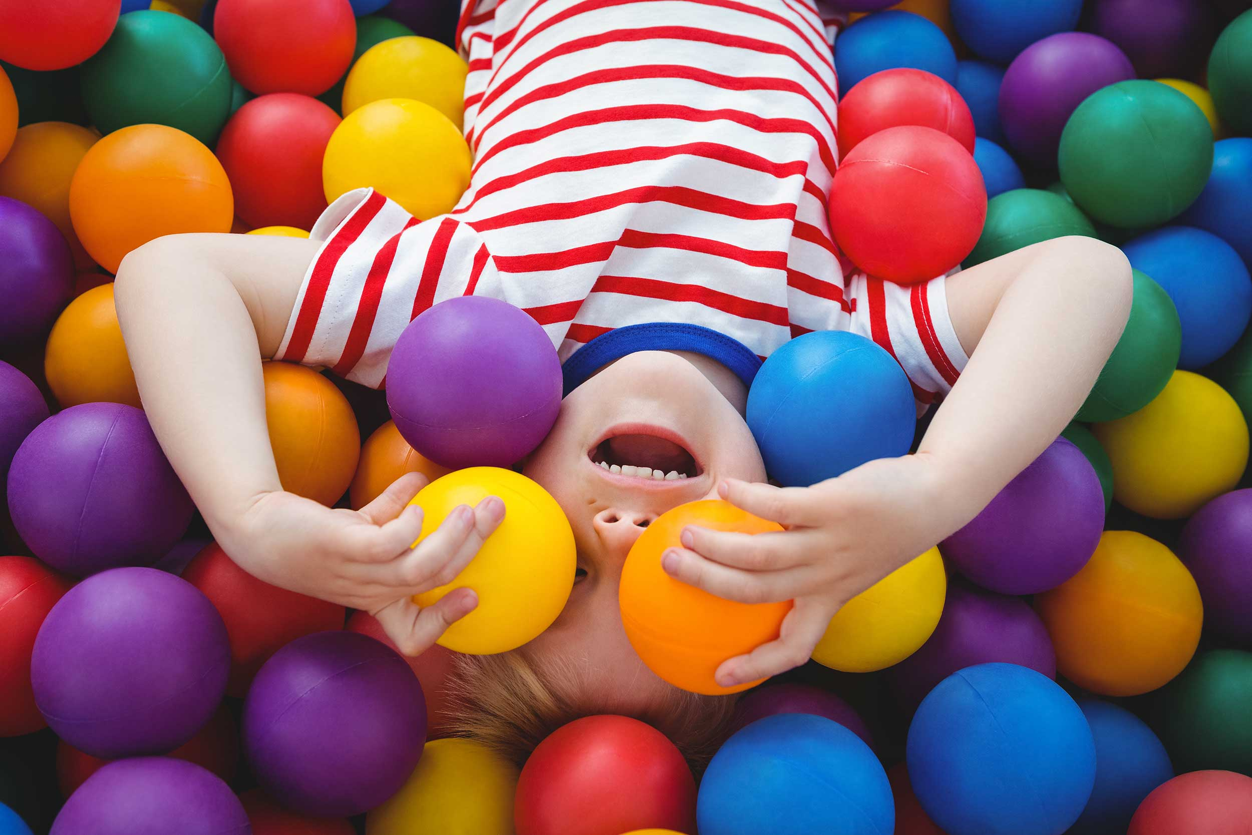 Kid in a colourful ball pit
