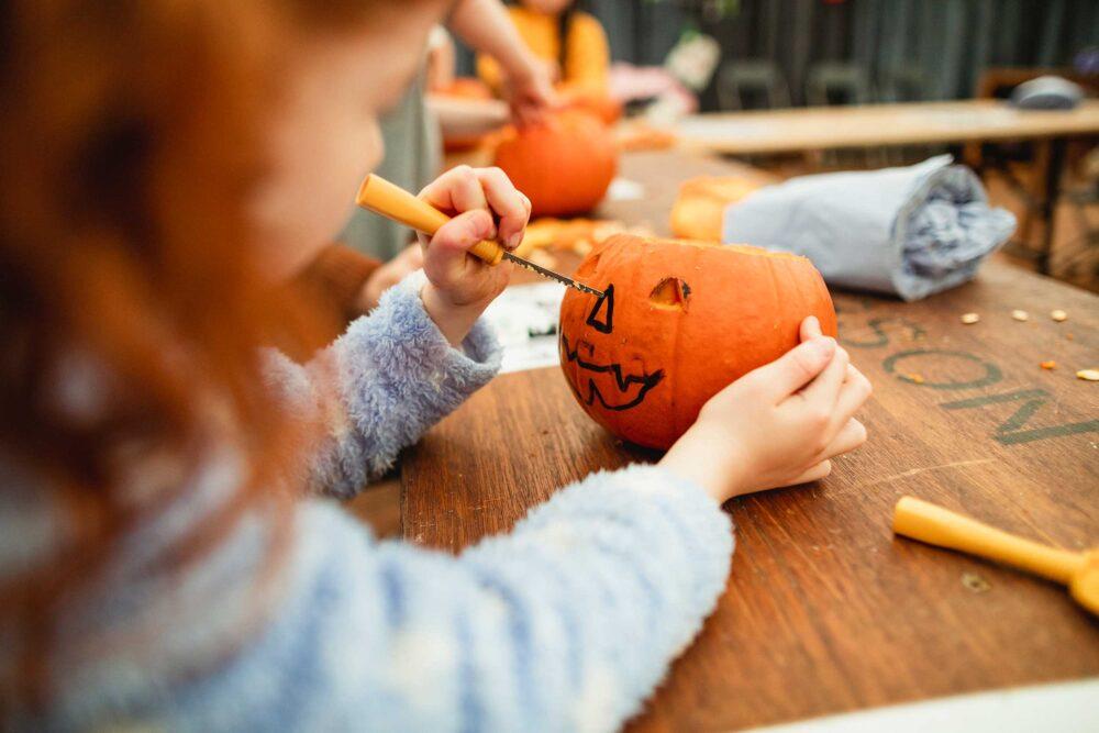 Child carving a pumpkin
